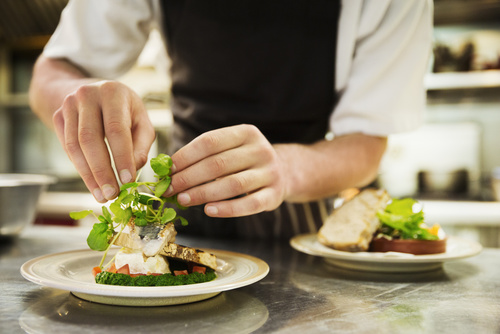 Close up of chef in kitchen adding salad garnish to a plate with
