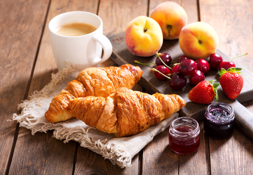 breakfast with croissants, coffee and fresh fruits